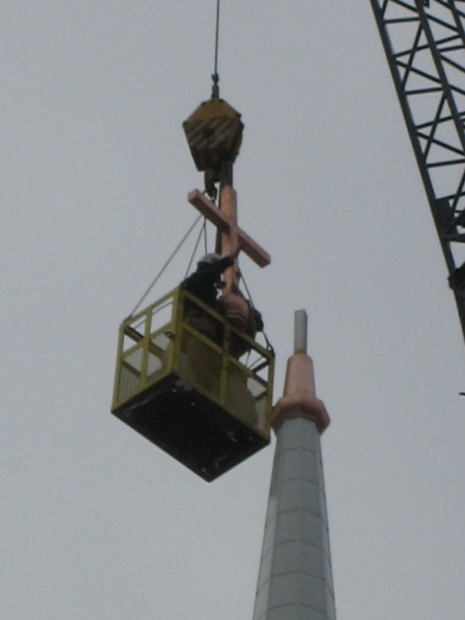 Crew installing the copper cross on top of the steeple