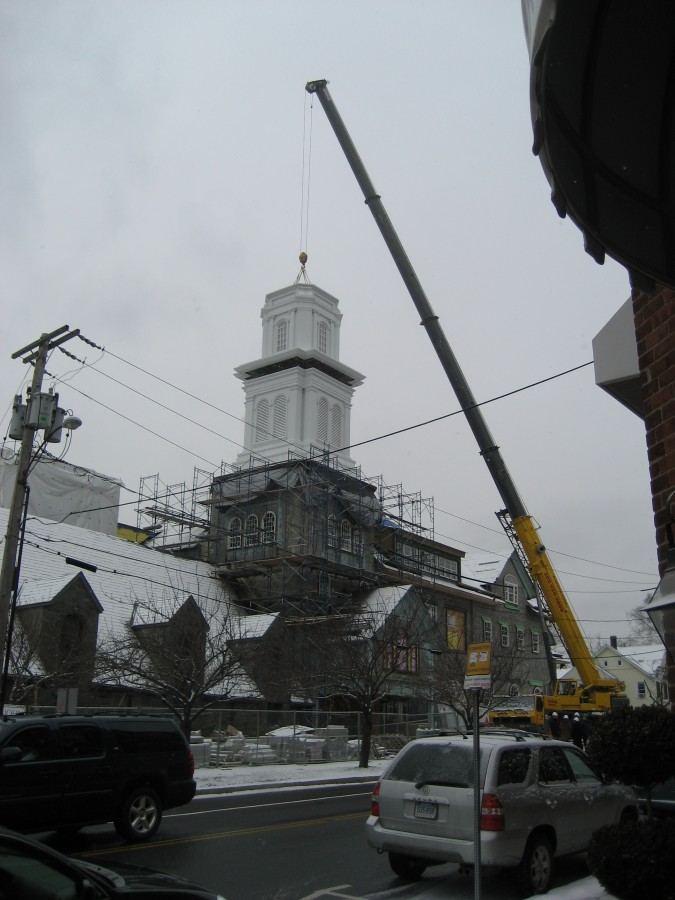 Louvered section of church steeple being lowered in place