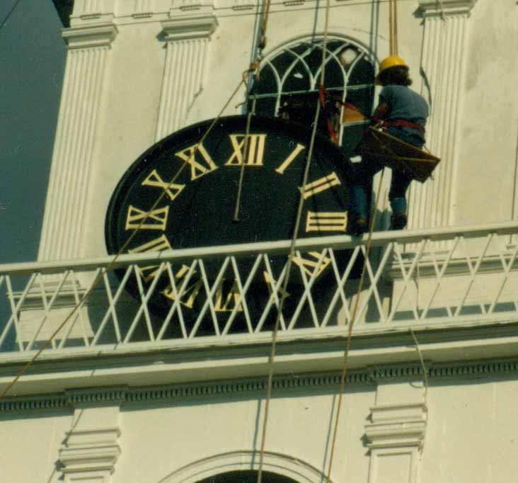 A historic reproduction of a clock face is hoisted into position with newly gilded roman numerals.